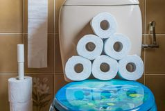 Pilha do papel higiênico empilhado no assento do armário de água, interior de um banheiro, fundo sanitário fotografia de stock royalty free