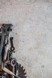 A pilha do vintage velho utiliza ferramentas incluir a chave, chaves inglesas, ferramentas, lâmina de serra e as peças sortidos c Foto de Stock