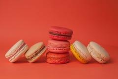 Pilha dos bolinhos de amêndoa coloridos empilhados acima como uma torre e macarons em seus dois lados no fundo pastel vermelho Foto de Stock Royalty Free