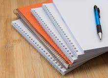 Pilha dos cadernos pessoais brancos e alaranjados do escritório Fotografia de Stock Royalty Free