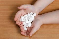 Pilha dos comprimidos brancos nas mãos da criança sobre o fundo de madeira vi foto de stock