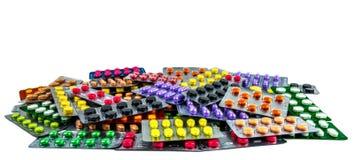 Pilha dos comprimidos da tabuleta isolados no fundo branco Comprimidos amarelos, roxos, pretos, alaranjados, cor-de-rosa, verdes  Imagens de Stock
