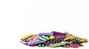 Pilha dos comprimidos da tabuleta isolados no fundo branco Comprimidos amarelos, roxos, pretos, alaranjados, cor-de-rosa, verdes  Fotos de Stock Royalty Free