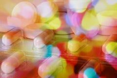 Pilha dos comprimidos na fantasia da cor com as cores psicadélicos que mostram a confusão ou a desorientação devido às drogas com Foto de Stock Royalty Free