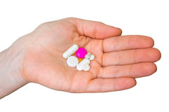 Pilha dos comprimidos na mão fêmea isolada no branco Fotografia de Stock Royalty Free
