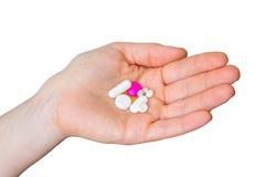 Pilha dos comprimidos na mão fêmea isolada no branco Foto de Stock Royalty Free
