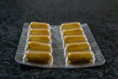 Pilha dos comprimidos no bloco de bolha com cápsulas imagem de stock