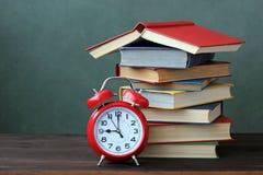 A pilha dos livros e do despertador na tabela De volta à escola Fotografia de Stock Royalty Free