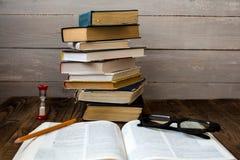 Pilha dos livros e os vidros e o lápis da ampulheta fotografia de stock royalty free