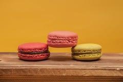 Pilha dos macarons coloridos empilhados acima na cor pastel amarela isolada Imagens de Stock