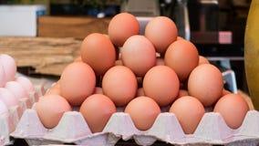 Pilha dos ovos da galinha na venda em sua caixa da caixa Cor de Brown imagem de stock royalty free