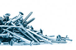 Pilha dos parafusos em um fundo branco Imagem de Stock