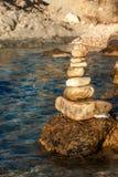 Pilha dos seixos na parte dianteira de mar em um dia bonito Pilha do seixo no litoral Pirâmide de pedra Pedras equilibradas do ze Fotos de Stock Royalty Free