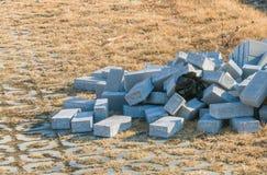 Pilha dos tijolos cinzentos que colocam na terra fotos de stock royalty free