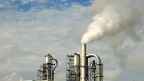 A pilha e as tubulações de fumo da fábrica sopram no ar Imagens de Stock