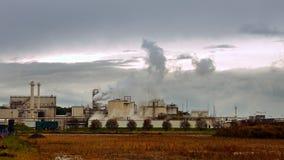 A pilha e as tubulações de fumo da fábrica sopram no ar Fotografia de Stock