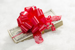Pilha envolvida de cem notas de dólar com a fita vermelha na neve Fotografia de Stock