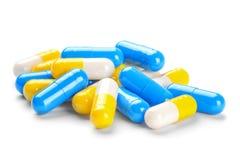 Pilha pequena de comprimidos amarelos médicos e de comprimidos azuis Fotografia de Stock
