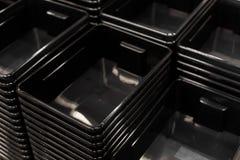Pilha preta dos recipientes plásticos em uma loja fotos de stock