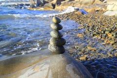 Pilha surpreendente de pedras no musgo verde no grupo de praia do beira-mar de equilíbrio do seixo na grande rocha Imagens de Stock
