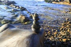 Pilha surpreendente de pedras no musgo verde no grupo de praia do beira-mar de equilíbrio do seixo na grande rocha Fotografia de Stock