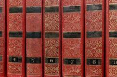A pilha velha de livros vermelhos na prateleira Imagem de Stock