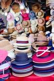 Pilhas coloridos coloridas de chapéus do verão para a venda no mercado de rua da noite fotos de stock