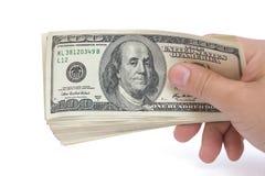 Pilhas da terra arrendada da mão da moeda de papel de 100 USD com trajeto de grampeamento Imagens de Stock Royalty Free