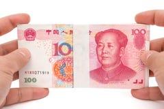 Pilhas da terra arrendada da mão de uma moeda de papel de 100 RMB com trajeto de grampeamento Imagens de Stock Royalty Free