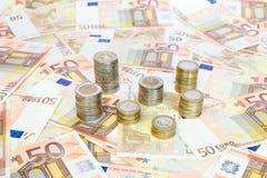 Pilhas das euro- moedas que estão em euro- notas Fotos de Stock