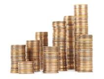 Pilhas das moedas de prata e douradas isoladas Fotos de Stock