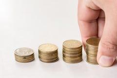 Pilhas das moedas do metal isoladas acima do fundo branco e da mão que guardam a pilha das moedas Fotografia de Stock