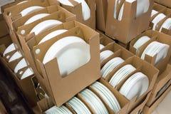 Pilhas das placas dadas forma brancas e redondas da porcelana em umas caixas imagens de stock royalty free
