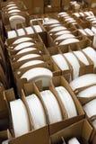 Pilhas das placas dadas forma brancas e redondas da porcelana em umas caixas imagens de stock