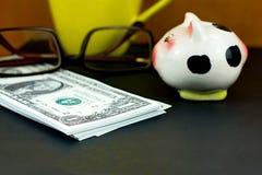 Pilhas de cédulas do dólar americano e do mealheiro pequeno no assoalho preto Fotos de Stock