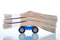 Pilhas de cédulas nas rodas de carro do brinquedo Fotografia de Stock