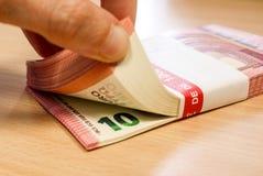 Pilhas de dez contas do Euro em uma mesa do pinho, sendo contado fotografia de stock royalty free