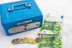 Pilhas de euro- moedas e cédulas em uma caixa do dinheiro Imagem de Stock