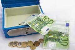 Pilhas de euro- moedas e cédulas em uma caixa do dinheiro Fotos de Stock