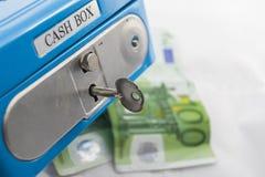 Pilhas de euro- moedas e cédulas em uma caixa do dinheiro Fotografia de Stock