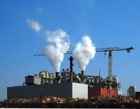 Pilhas de fumo e um guindaste em uma fábrica Fotografia de Stock Royalty Free