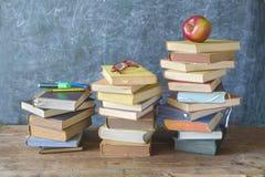 Pilhas de livros, maçã, especs., de volta ao conceito da escola foto de stock