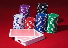 Pilhas de microplaquetas de póquer com cartões de jogo Fotografia de Stock Royalty Free