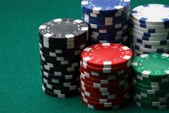 Pilhas de microplaquetas de póquer em uma superfície verde. Fotos de Stock Royalty Free