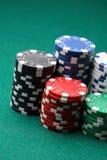 Pilhas de microplaquetas de póquer em uma superfície verde. Imagens de Stock Royalty Free