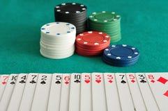 Pilhas de microplaquetas de pôquer com uma plataforma de cartões pulverizados para fora Foto de Stock