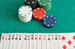 Pilhas de microplaquetas de pôquer com uma plataforma de cartões pulverizados para fora Foto de Stock Royalty Free