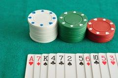 Pilhas de microplaquetas de pôquer com uma plataforma de cartões pulverizados para fora Imagem de Stock