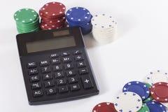 Pilhas de microplaquetas de pôquer e de calculadora preta Fotografia de Stock