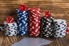Pilhas de microplaquetas de pôquer com cubos e de cartões em um de madeira Imagem de Stock
